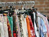 image of flea  - vintage clothes hanging in the flea market of used things - JPG