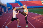 foto of race track  - young runner sporty woman relaxing and stretching on athletic race track - JPG
