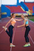 picture of race track  - young runner sporty woman relaxing and stretching on athletic race track - JPG