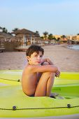 stock photo of preteens  - preteen handsome boy in the rubber surf boat on the red sea beach and yaht background - JPG
