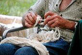stock photo of macrame  - Talented aged hands weaving macrame art to sell at market - JPG