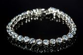 stock photo of precious stones  - Beautiful golden bracelet with precious stones on black background - JPG