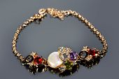stock photo of precious stones  - Beautiful golden bracelet with precious stones on grey background - JPG
