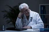 stock photo of depressed  - Aged doctor with depression sitting alone in cabinet - JPG