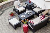 image of comfort  - High Angle View of Upscale Patio Set Dark Wicker Luxury Furniture with Comfortable Cushions on Outdoor Stone Patio of Affluent Home - JPG