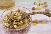 stock photo of viagra  - Walnuts hazelnuts and honey in a glass dish with a vintage wooden spoon on a pink tablecloth - JPG
