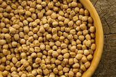 stock photo of chickpea  - bunch of chickpeas in a bowl on old wooden background - JPG