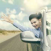 image of waving hands  - Successful young businessman driving a car while waving hand through the window - JPG
