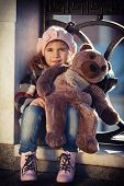 stock photo of beret  - little girl in a pink beret sits at a fencing of the bridge and holds a toy bear in hand - JPG