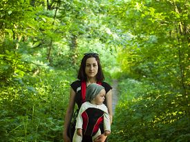 picture of sling bag  - Young mother walking in the Park and holding a small child in a Baby Carrier bag - JPG
