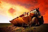 image of power-shovel  - Yellow tractor on golden surise sky - JPG