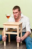 Drunken Man Sitting On Floor With Glass Of Alcohol And Holding Stool