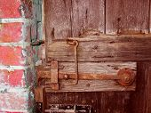 foto of gare  - A Rusty latch on garden gate with bolt hook and wall - JPG