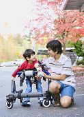stock photo of physically handicapped  - Teen boy with disabled little brother in walker out walking - JPG