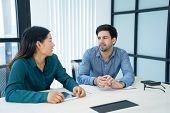 Two Serious Coworkers Talking At Conference Table. Caucasian Male And Asian Female Employees Waiting poster
