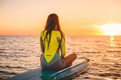 Woman Relaxing On Stand Up Paddle Board, Quiet Sea With Warm Sunset Colors. poster