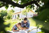 Mature Father And A Small Daughter Outside, Planning Wooden Birdhouse Or Bird Feeder. Sketches Makin poster