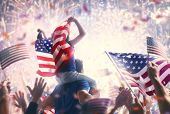 Patriotic holiday. Child sitting on shoulders of her father and  holding the Flag of the USA. Americ poster