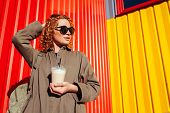 Hipster Young Woman With Curly Red Hair Drinking Coffee Against Red And Yellow Wall. Tourist With Ba poster