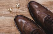 Stylish Mens Accessories. Brown Shoes With Cuff On Wooden Background poster
