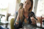 Girl doing makeup retouching at work poster