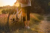 Girl Travel By Bicycle In Sunset. Girl Travel Alone By Bicycle In Countryside Landscape. Traveler Cy poster