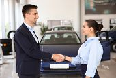 Young Salesman Working With Client In Car Dealership poster