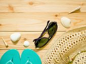 Flip-flops, Sunglasses And Beach Hat On Wooden Background poster