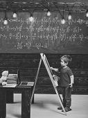 Happy Kid Having Fun. Little Boy Writing On Chalkboard. Side View Kid In Front Of Green Board With M poster