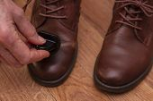 Leather Shoe Care. Applying Shoe Polish To Brown Shoes. Shabby Leather Brown Shoes. poster