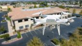 Unmanned Aircraft System Quadcopter Drone In The Air Near Corporate Industrial Building. poster