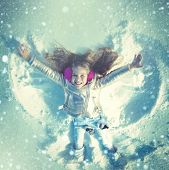 Funny Kid Making Snow Angel. Child Girl Playing And Making A Snow Angel In The Snow. Top View poster