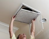 image of hvac  - Senior male reaching up to open filter holder for air conditioning filter in ceiling - JPG