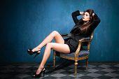 Постер, плакат: чувственный некурящих молодая женщина в черный смокинг и туфли на каблуках сесть на кресло в голубой комнате с ti