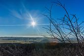 View Of Winter Landscape On A Bright Day With Sun Shining On A Blue Sky With Condensation Trails. Br poster