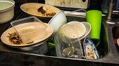 Dirty Dishes, Utensil, Plastic Container And Food Waste Piled In A Metal Sink At The Kitchen. poster