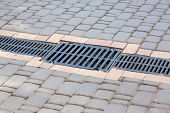 A Lattice Of A Drainage Paving System On A Path Made Of Square Stone Tiles, Close Up Of A Rainwater  poster