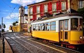 Lisbon Portugal. Yellow vintage tram driving by street of paving stones in district Alfama. Cityscap poster