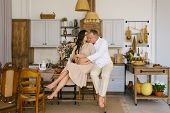 A Young Married Couple Hugs While Sitting On A Table In The Kitchen. The Husband Hugs His Pregnant W poster
