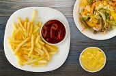 French Fries With Ketchup On A Wooden Background. French Fries On A White Plate poster