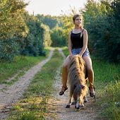 Teenage Girl Riding On A Pony Horse Along A Country Road poster