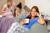 stock photo of slumber party  - Teenager girls reading and drinking at slumber party - JPG