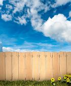 3D rendering of a wooden fence with blue sky in the background, ideal for inserting a message or ima