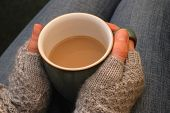 picture of lap  - A woman in a warm jumper holding a cup of tea or coffee on her lap - JPG