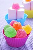 gumdrops of different colors and marshmallows in bowls of different colors on a purple woven backgro