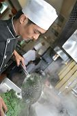 Chef Cooking And Holding Pepper Mill poster