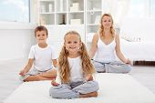 stock photo of three life  - Kids doing yoga relaxing exercise with their mother at home - JPG