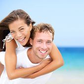 Happy couple on beach fun summer vacation. Multiracial Young newlywed couple piggybacking smiling jo