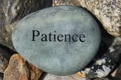 stock photo of reinforcing  - Positive reinforcement word Patience engrained on a rock - JPG