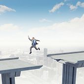 picture of gap  - Businessman jumping over a gap in the bridge as a symbol of bridge - JPG